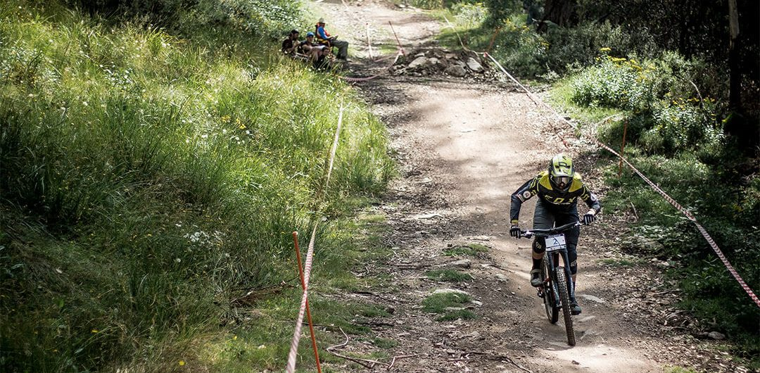 Downhill mountain bike racer pedalling at Mount Buller tiny