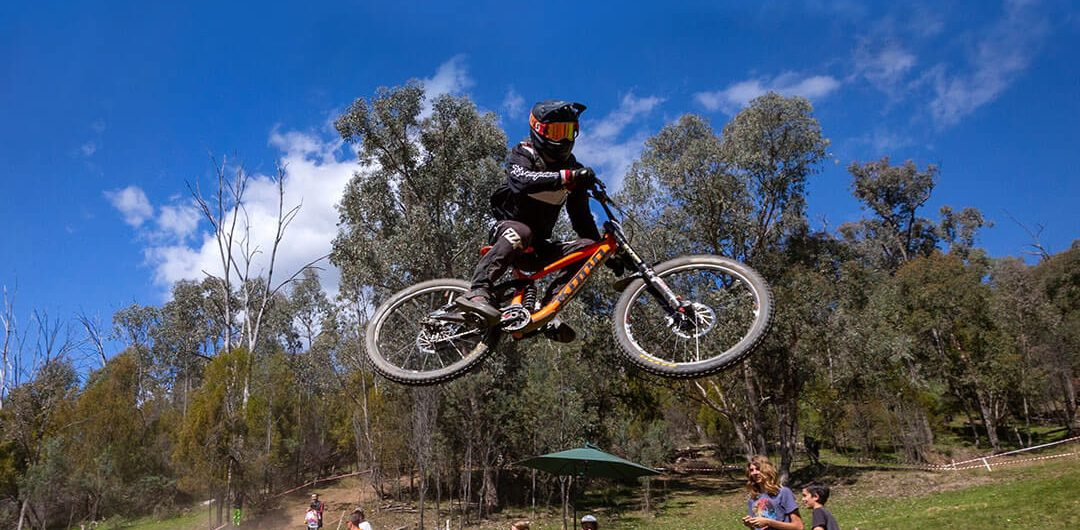 Victorian Downhill Series downhill mountain biker doing a jump at Mount Beauty VDHS