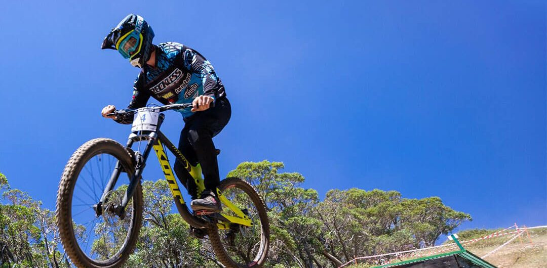 Victorian Downhill Series downhill mountain biker doing a jump at Mount Buller VDHS